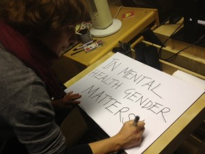 A women is writing text on a banner. It read 'in mental health gender matters'.